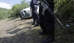 Police officers stand guard on a road near the location where the clandestine graves were found at Las Parotas, in the outskirts of Iguala