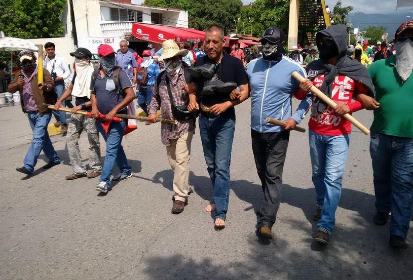 Manifestantes en Iguala obligan a policía a marchar descalzo